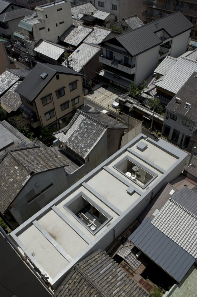 This aerial view highlights the close proximity of neighboring buildings, with the home standing out with its raised level and pair of private patio spaces fully open to the sky.