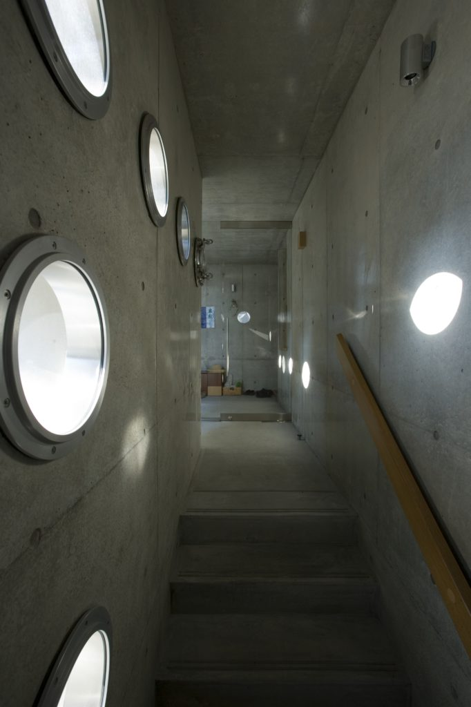 At the top of the wood rail stairs, we see sunlight beaming through, casting moving dots on the opposing walls.