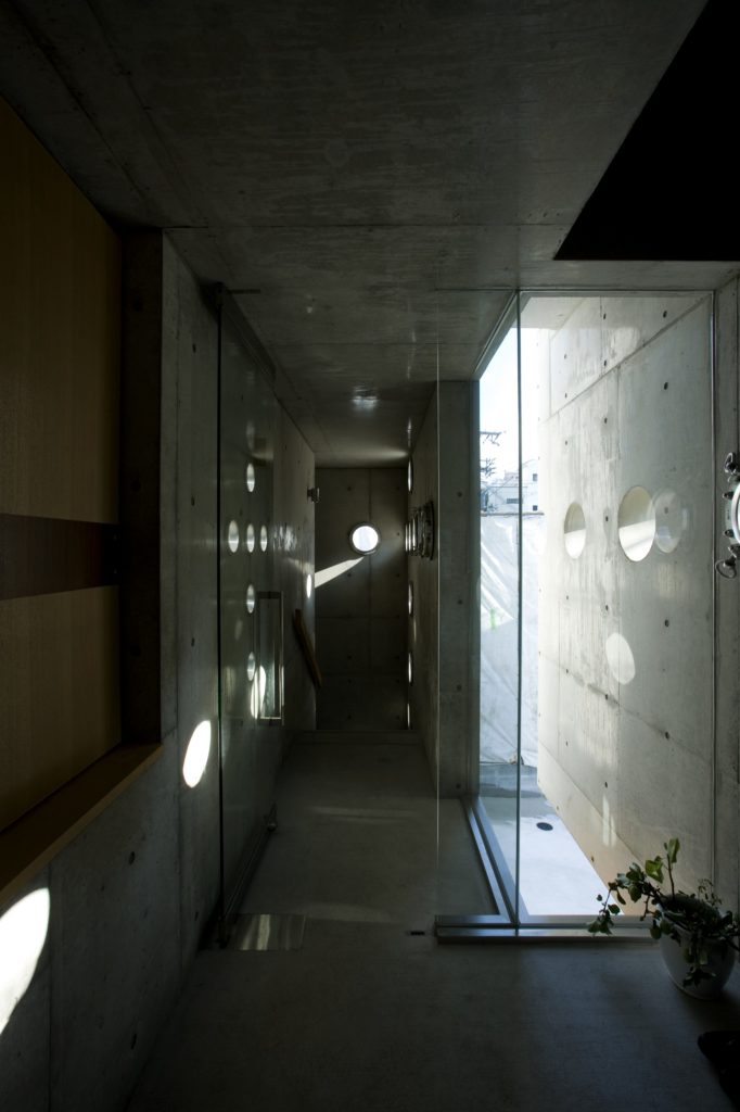 Intersection within the home features floor to ceiling glass for views of the secluded patio space, highlighting the interplay of multiple crossing light hole paths.