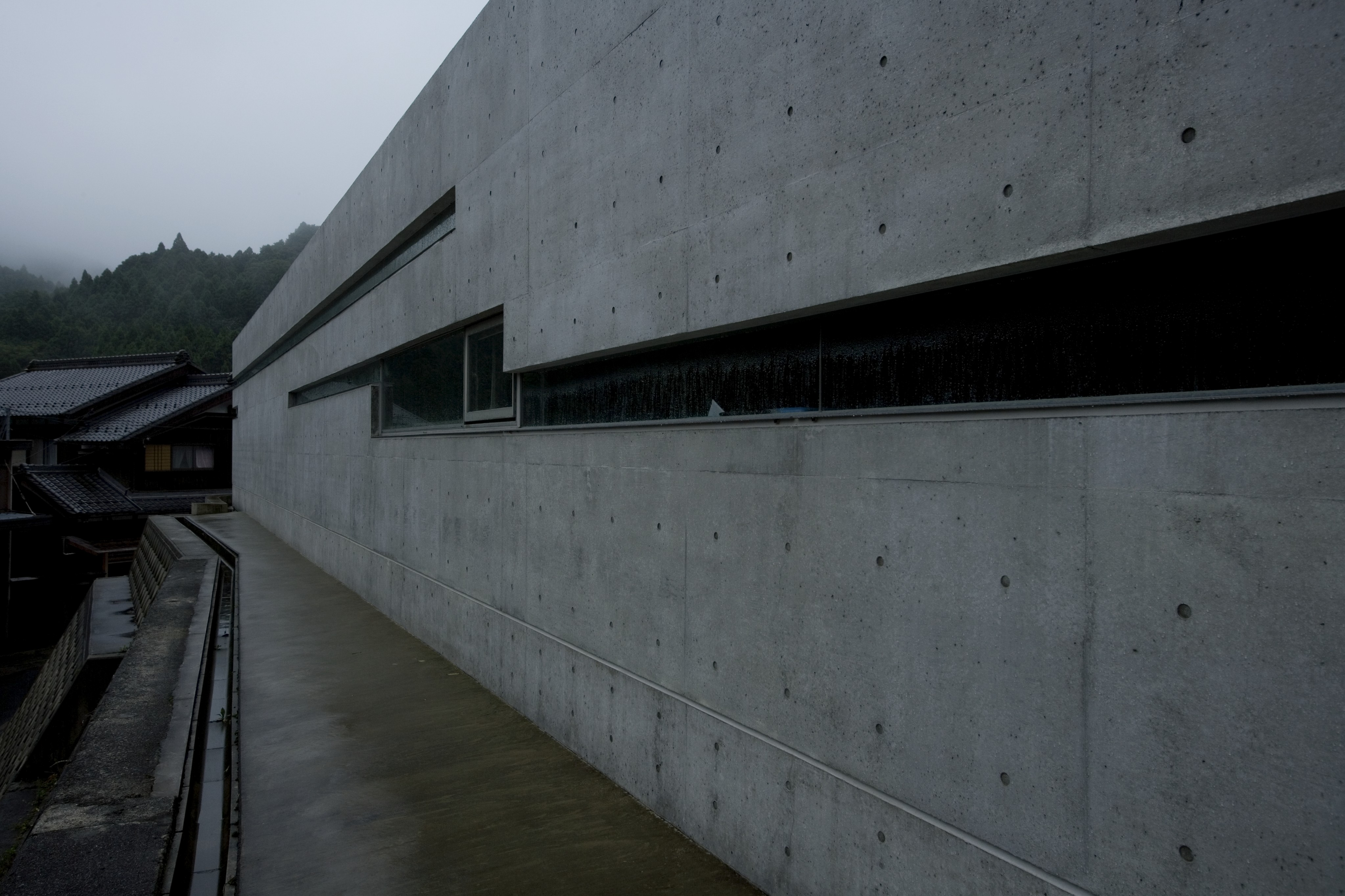 From above the retaining wall, we see the concrete facade and slit windows heavily obscured. The uniform expanse of grey hides the warm natural tones within.