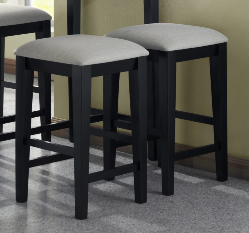 Grey kitchen counter stools with wood legs.