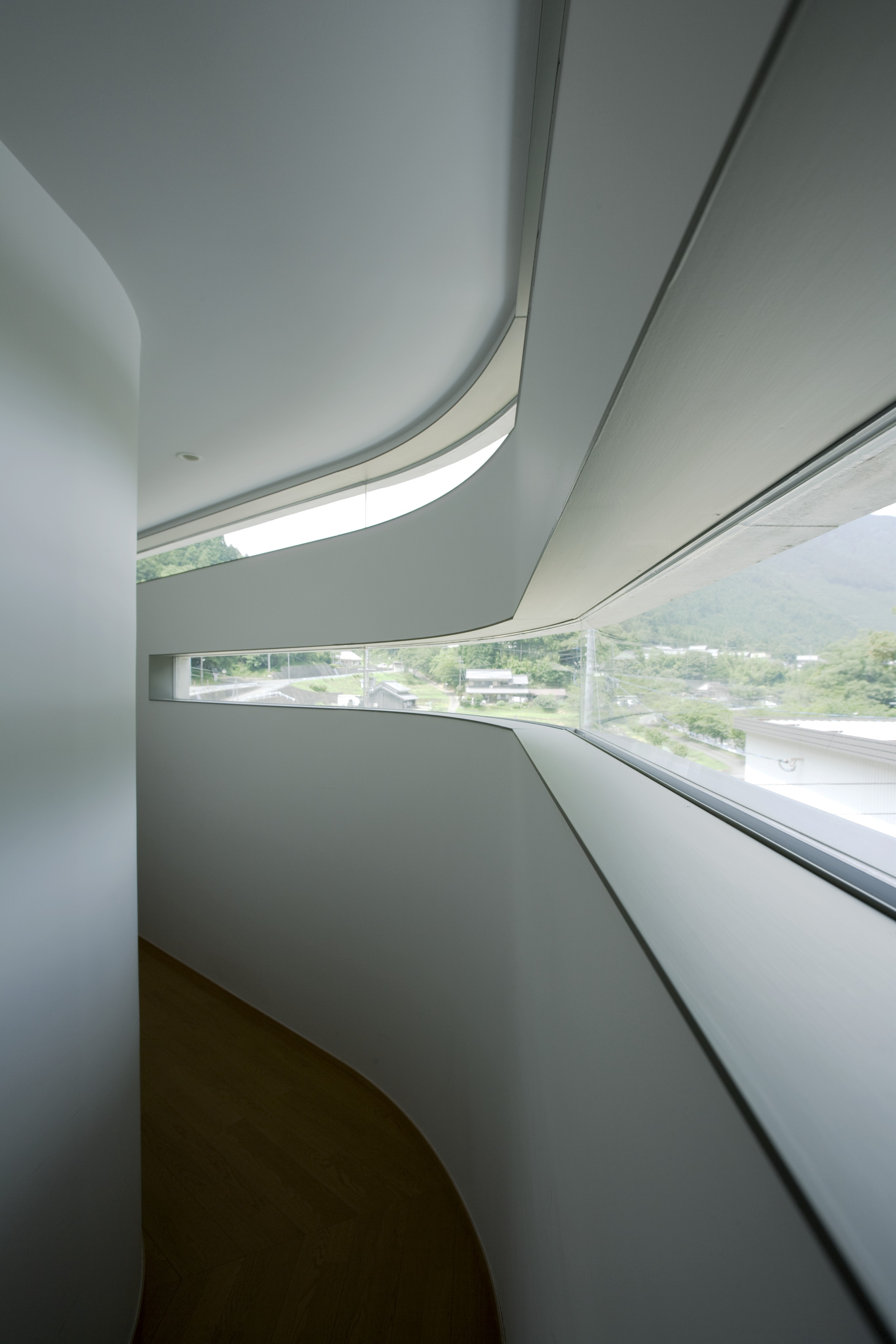 Main wraparound hallway holds expansive views through the slit windows, curving through the structure on every side.