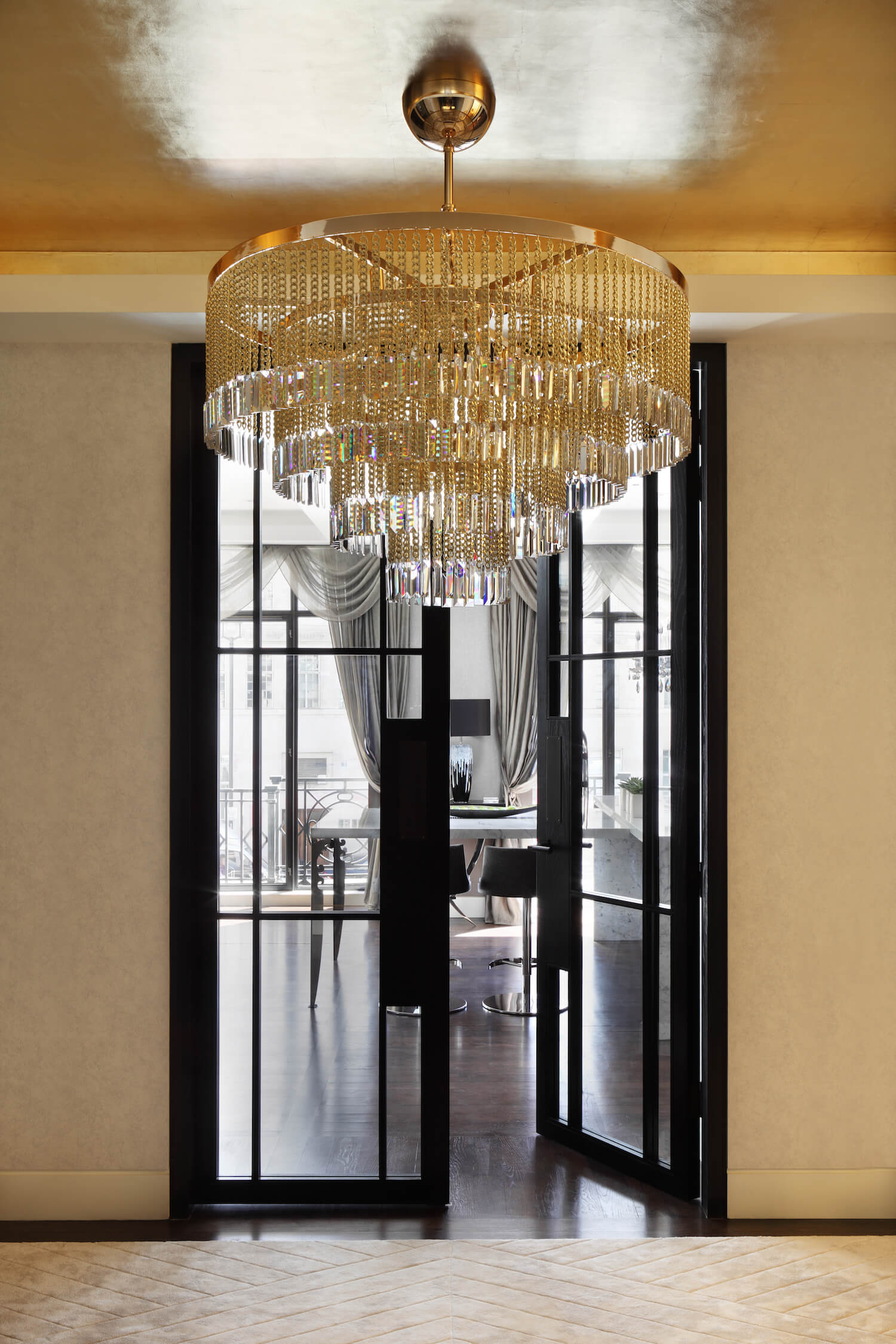 Handmade in Italy, an oversized chandelier adorned with rows of gold chains and crystal pendants sets a bold, opulent tone for the rest of the apartment, right in the entryway.
