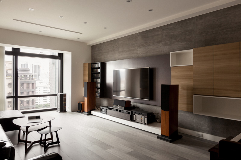 Along with the lower white wood tier floating above the hardwood flooring, we see an array of minimalist natural wood cabinetry and white wood shelving throughout the media wall.