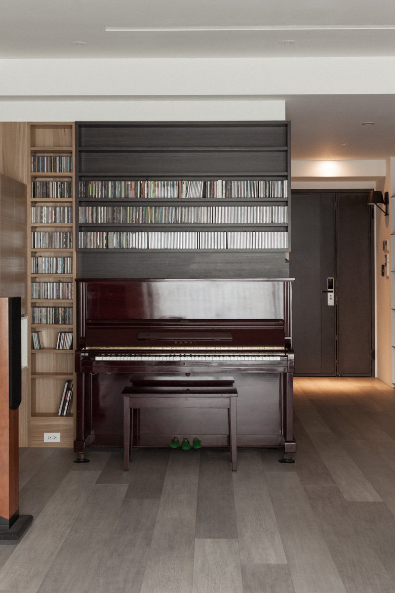 Before the main entrance, we have this classical upright piano standing below an immense set of media shelving in both natural and dark stained wood tones.
