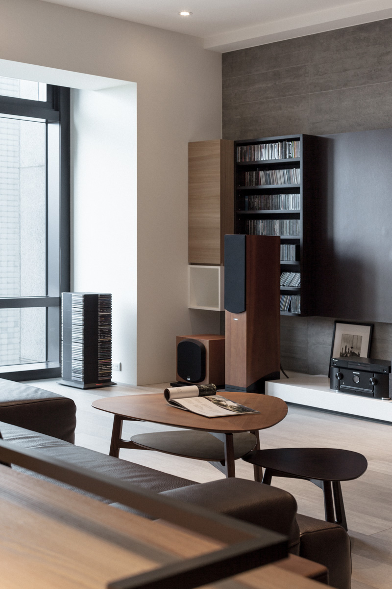 The unique tiered coffee table stands before the minimalist entertainment center, with an array of shelving in white, black, and natural wood tones.