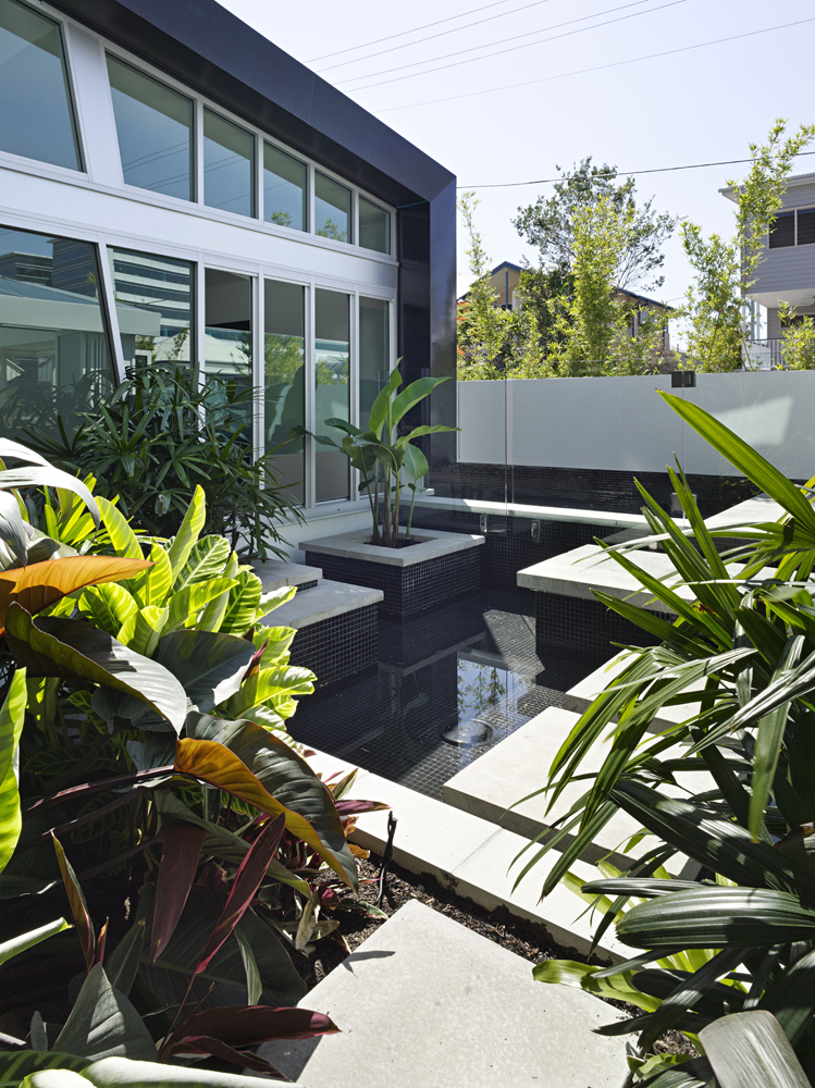 This rooftop garden features a tiered fountain wrapped in greenery, right outside the wraparound sliding glass panels.