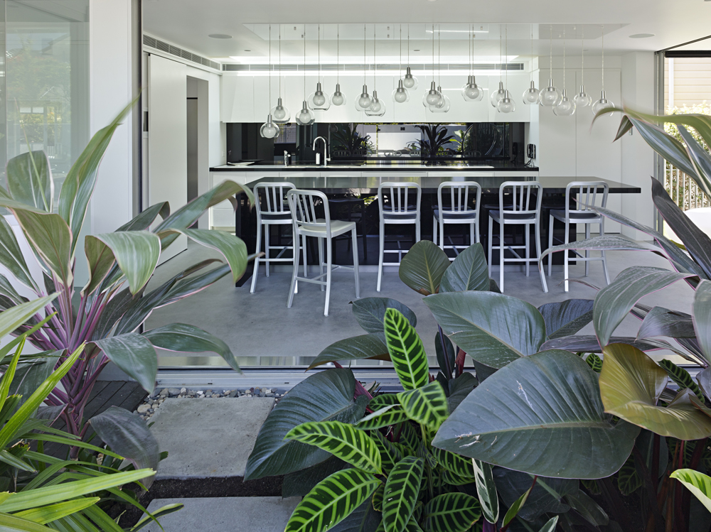Gazing over the greenery on the garden patio through open glass kitchen wall, we see the full breadth of the spherical glass lighting over the ample black island with dining space and set of metallic tall chairs.