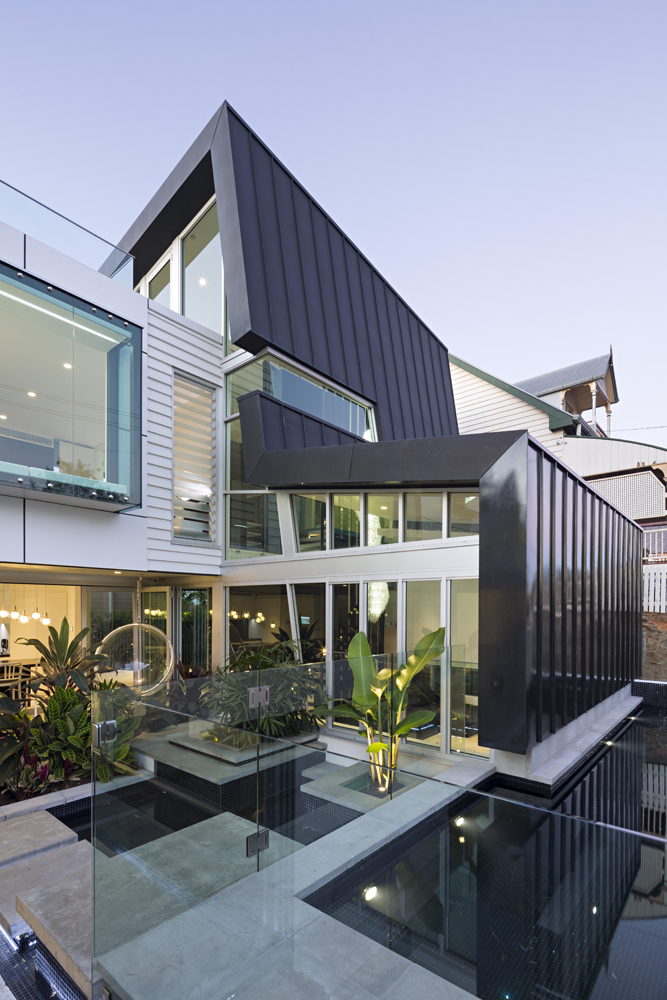 Rooftop view clearly showcasing the modernist addition, wrapping the home in steel and glass.