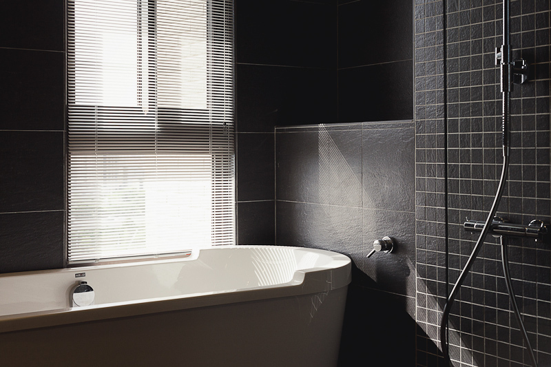 The shower is defined by an all-glass enclosure, with smaller black tiles inside.