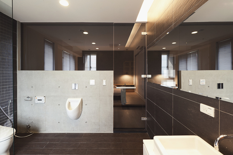 As part of the primary bedroom suite, the bathroom is defined by a low concrete wall surrounded by glass panels, including door. Vanity mirror runs length of the space.