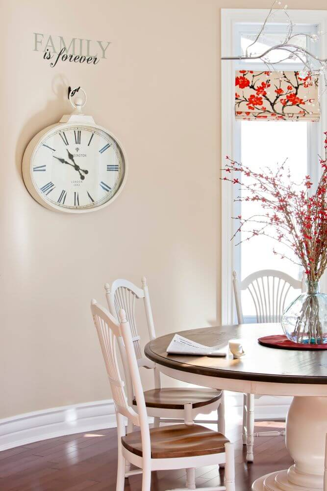 Smaller informal dining space stands a traditional round wood table with white body and natural top at center.