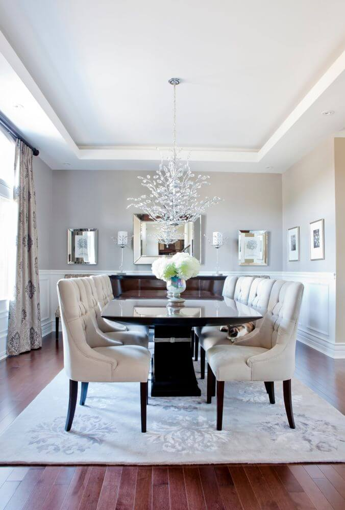 The living room features opulent details circling a black Hudson dining table over the rich hardwood flooring continued from the central living room.