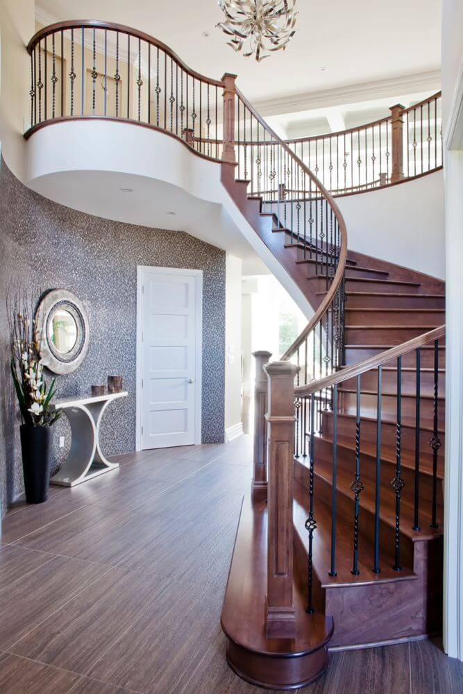 Main staircase is a beautifully curved dark wood design, with wrought-iron railing supports. Landing at a dark hardwood floor, this central hall space features artful metallic decorative table and mirror against patterned wall, while daylight beams in through large living room windows in background.
