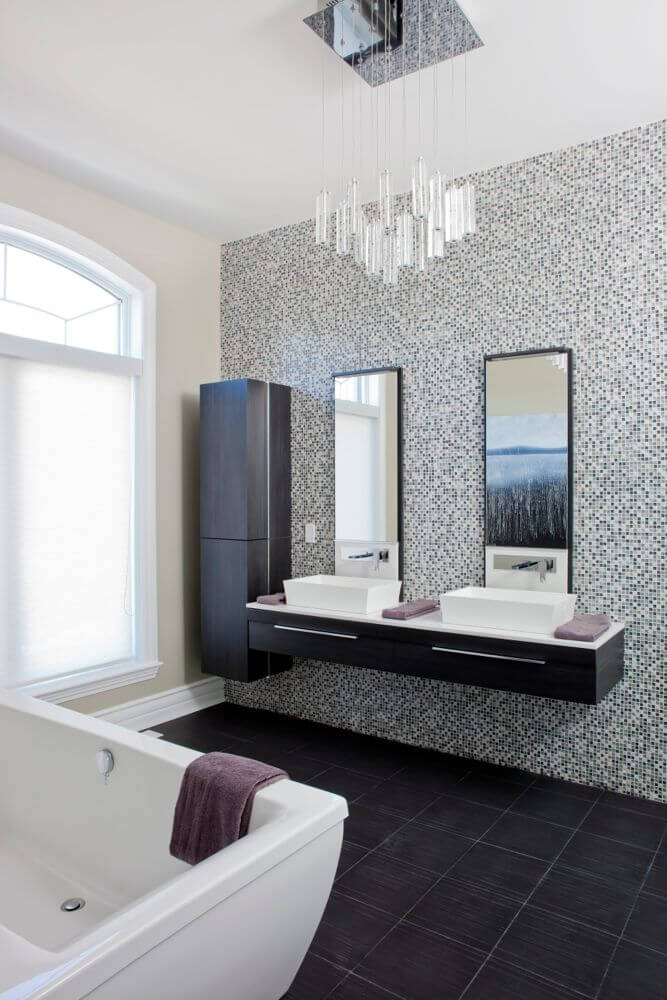 Dual vessel sink, black wood vanity stands on micro-tile wall above dark tile flooring, with matching vertical cabinet at left.