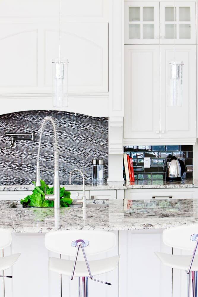 Close look at the kitchen reveals a multitude of subtle textures. Micro-brick tile backsplash over the range, larger black brick tiles under cupboards at right, rich marble countertops throughout, and glass cylinder lighting hanging above.