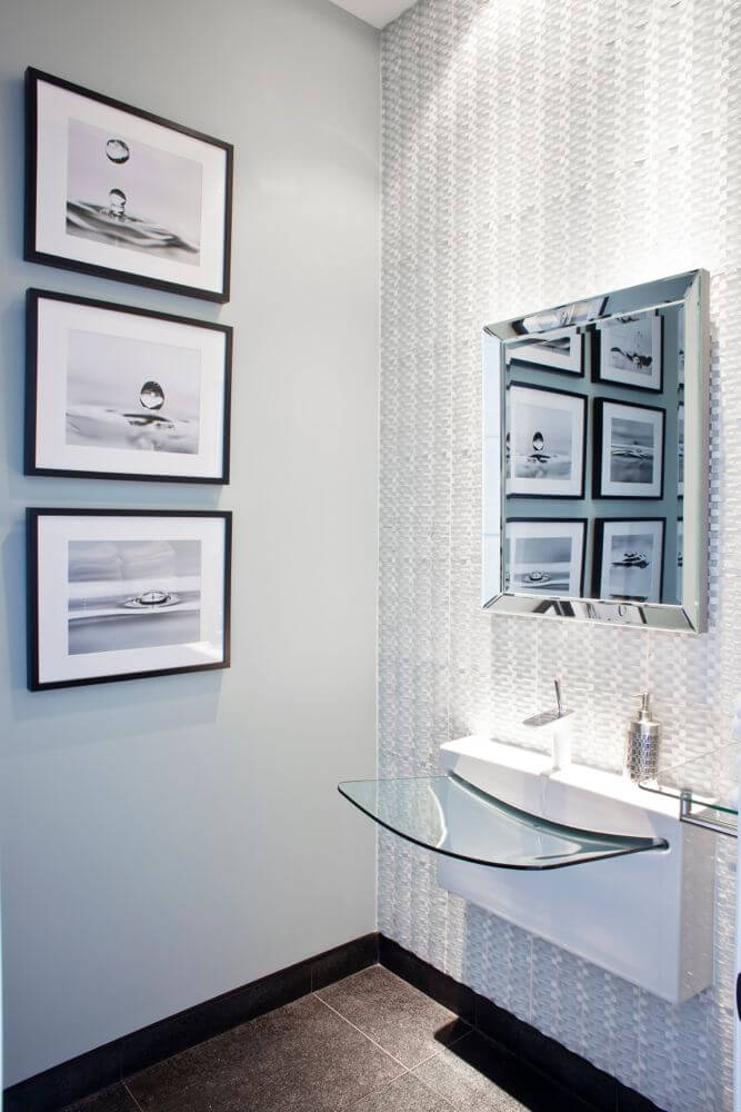 Bathroom features this striking modern sink design floating above dark tile flooring. Wicker-textured wall holds chrome framed mirror next to white wall.