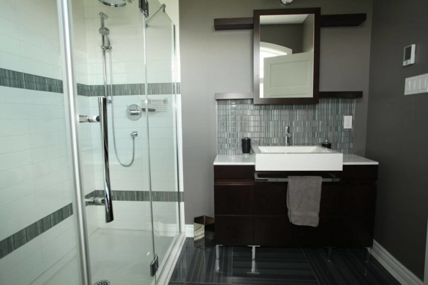 Head on view of the vanity, showing unique dark wood mirror frame and shelving built into wall.