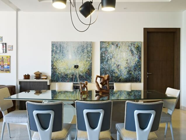 Dining room set, with immense glass-top table standing beneath black recycled component chandelier, holds the pair of aforementioned paintings next to dark natural wood door.