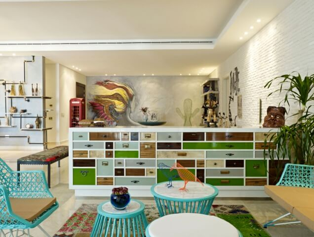 "In the ""greenery"" space, various bright teal pieces of furniture stand over a patchwork rug, with the large dividing cabinet defining the area."