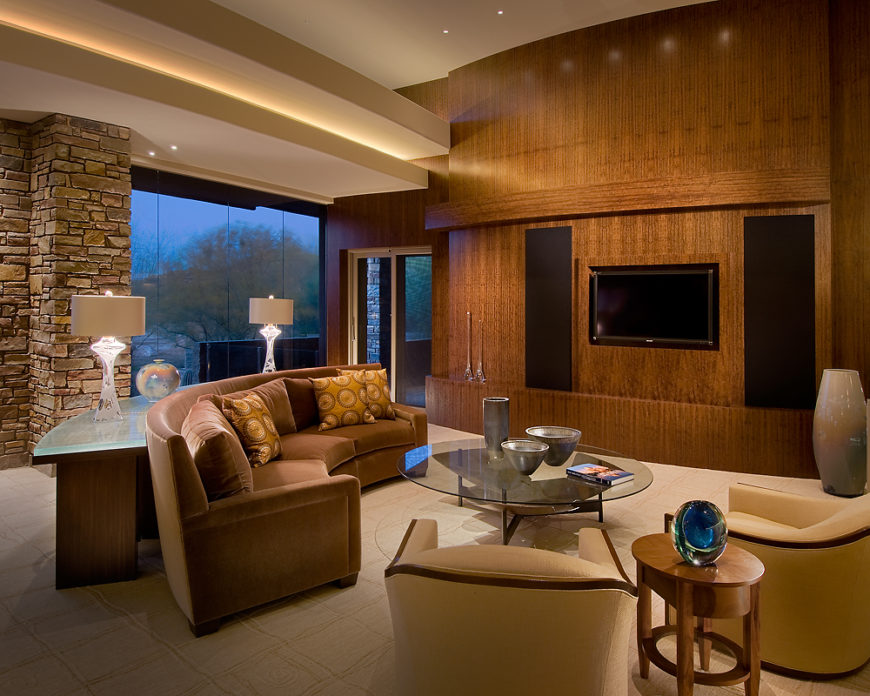 Massive, figured walnut entertainment wall stands over the living room, featuring a glass coffee table surrounded elegant seating options. Curved table with cast glass top hugs the C-shaped sofa.