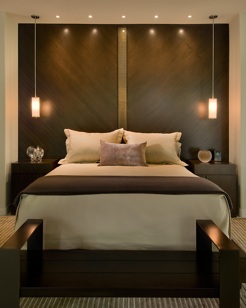Primary bed features a dark walnut headboard wall bisected by glass tile and matched with flanking bedside tables.