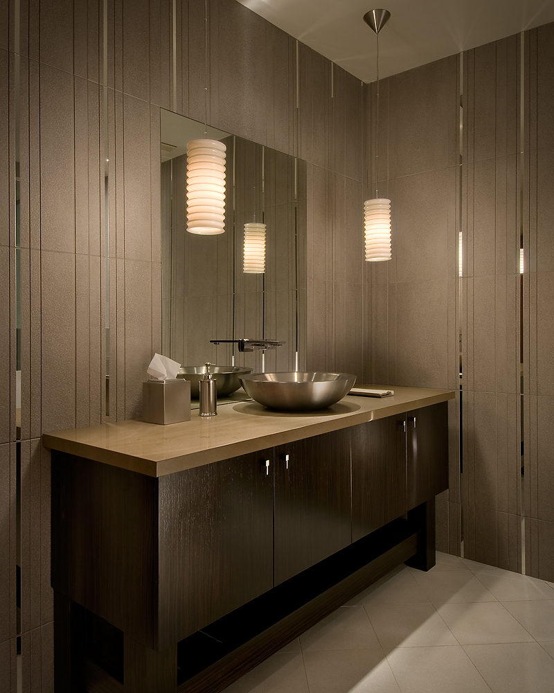 Bathroom features a custom vanity with steel vessel sink over a quartzite slab countertop. Brown tiled walls are intercut with mirrored strips.