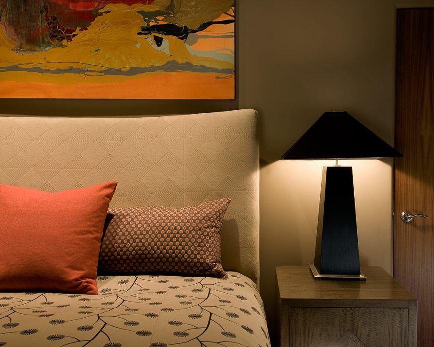 Guest bedroom features dark wood beside dresser with minimalist black lamp beside a plush beige headboard and poppy patterned duvet.