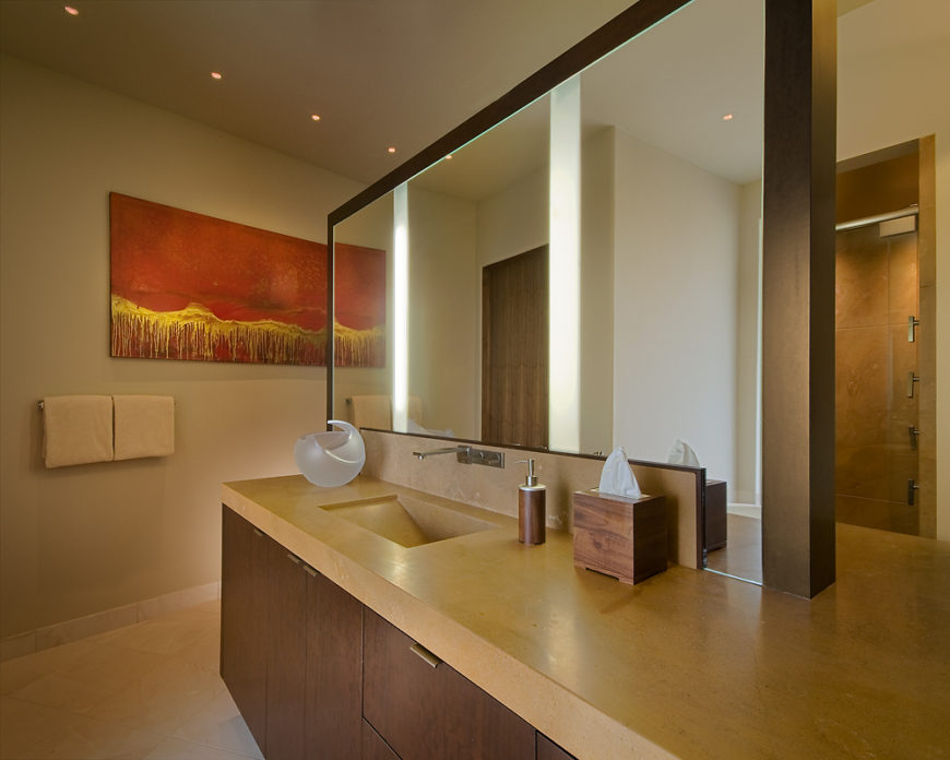 Bathroom features centralized vanity with limestone countertop holding a built-in sink, below mirror with embedded lighting.
