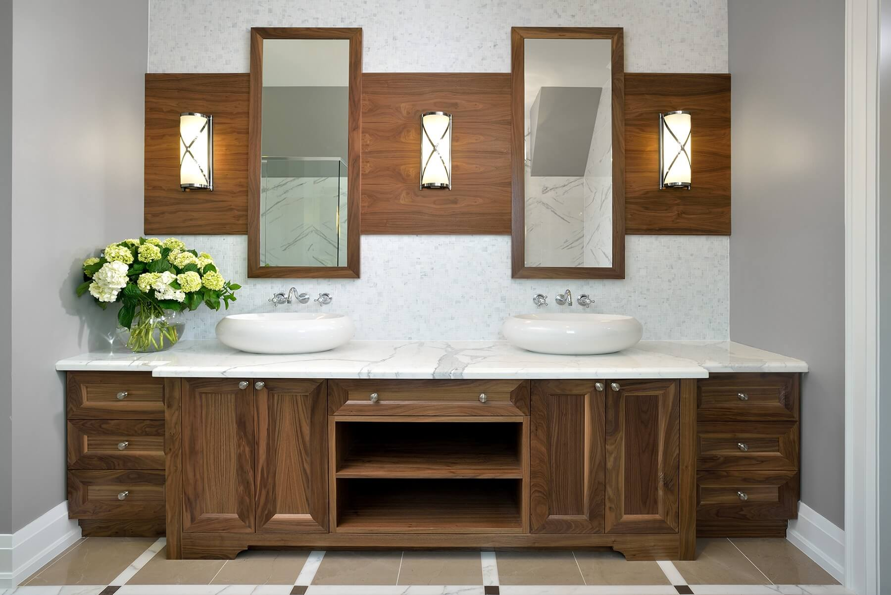 Dual vanity features large white vessel sinks over marble countertop, with a pair of individual mirrors hung on sleek wall mounted wood paneling.