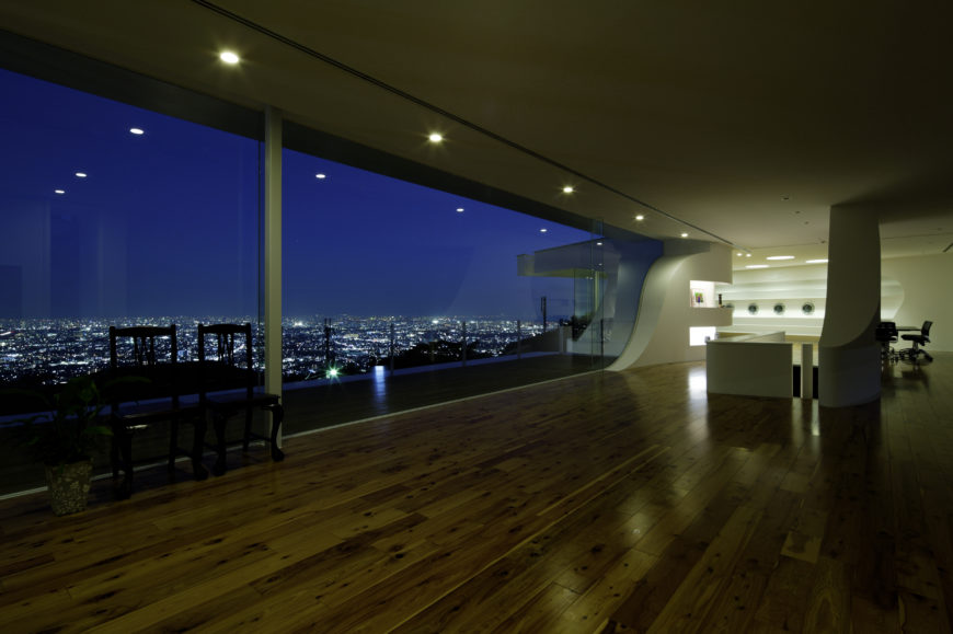 At night, we see the subtle recessed lighting that glows from ceiling and shelving alike, along with the carved organic shapes throughout the home. An expanse of city lights is seen in the distance.