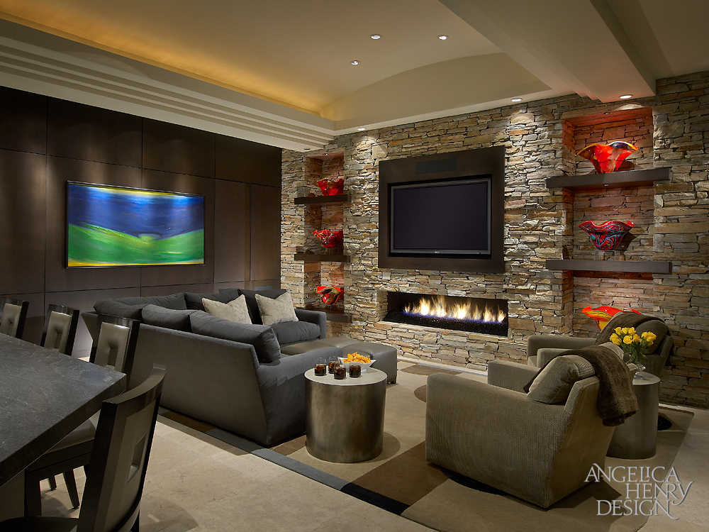 The lush family room features a stone wall with built in dark wood shelving flanking the fireplace and mounted television. Dark espresso oak paneled wall at left conceals media devices, while L-shaped sectional and a pair of armchairs provide comfort.