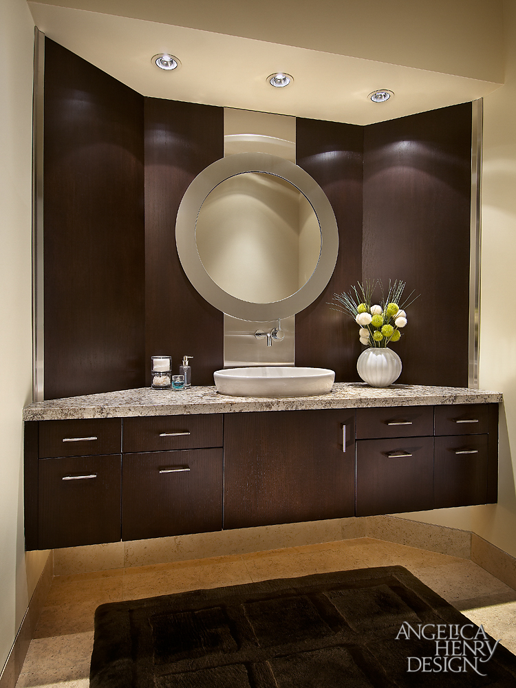Primary bath features this vanity in dark wood paneling, with circular mirror and stainless steel strip at center behind vessel sink.