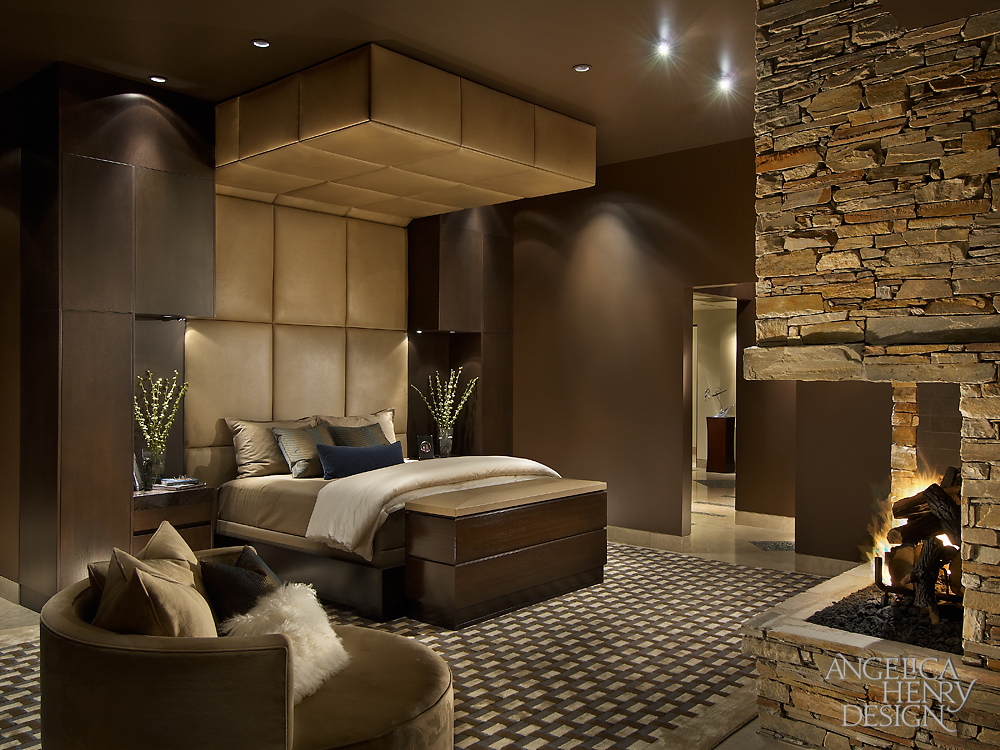 Luxurious primary bedroom offers a taupe bed with custom tufted headboard facing the corner bricked fireplace. It includes an upholstered rounded chair accented with pillows.