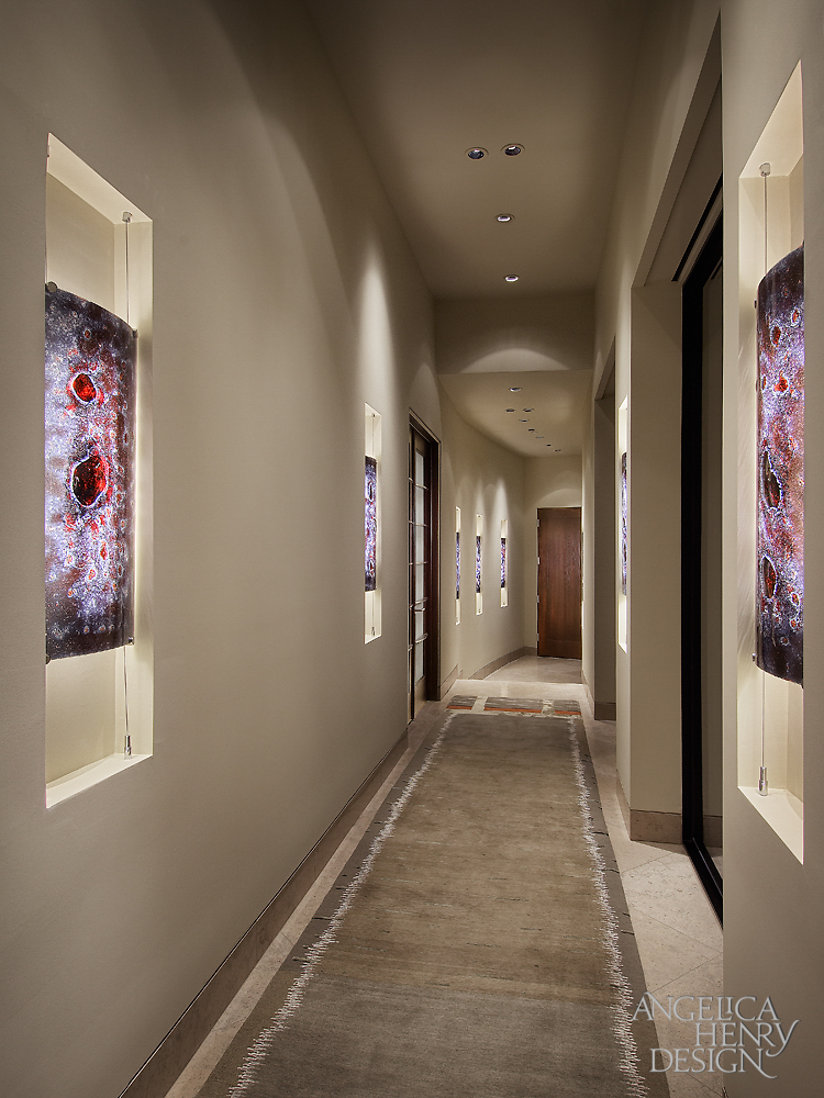 Gallery styled hallway features unique glass pieces set into inner-lit niches along the walls. Unobtrusive recessed ceiling lighting illuminates the space.