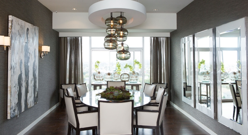 The opulent dining room wraps detailed black wood and white cushion chairs around an oval shaped table, below carved ceiling with glass sphere chandelier at center. Dark grey walls and dark natural hardwood flooring contrast with the white tones.