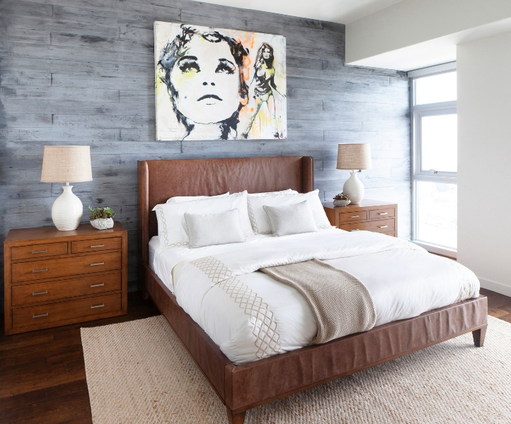Another bedroom features unique details, including leather-clad bed frame, twin natural wood dressers, and a Raquel Welch art piece hanging on grey stained wood wall.