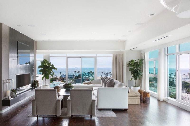 The living room has views all around through floor to ceiling glass and sliding patio doors. Large gas fireplace surround stands before white sectional and pair of contemporary chairs over lush, dark hardwood flooring.