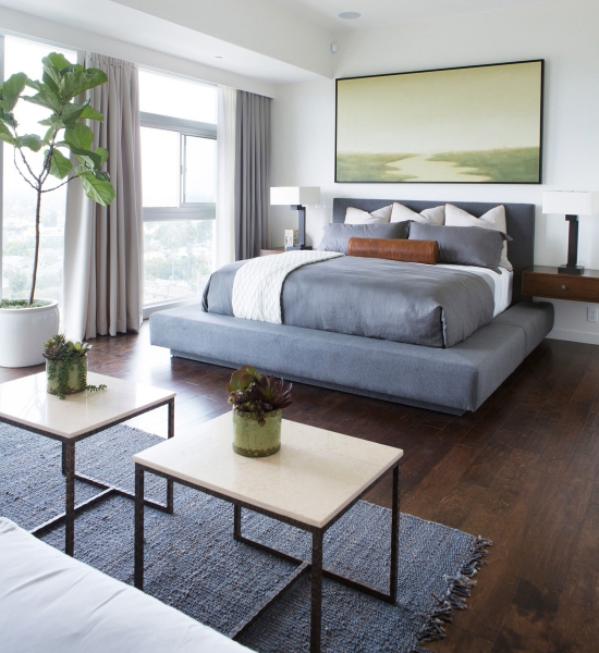 This bedroom suite pairs grey tones, on platform frame bedding and rug, with the dark natural hardwood flooring and white tones seen throughout the hame. Bed stands next to full height windows and is flanked by floating wall-mounted tables.