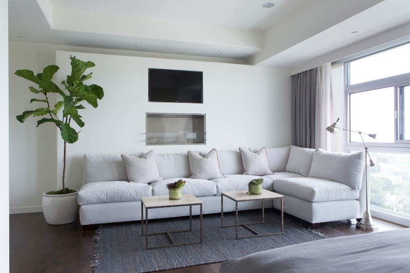 The bedroom suite contains a large cushioned white L-shaped sofa, with a pair of natural wood topped coffee tables, beneath wall mounted gas fireplace and television.