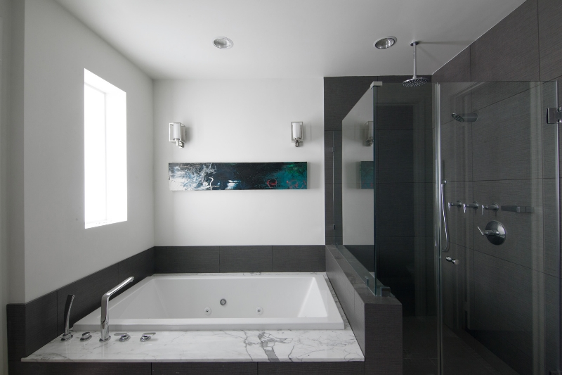 All-glass shower and large jacuzzi tub wrapped in grey tile beneath window, painting, and wall sconces.