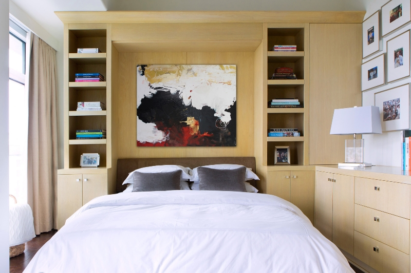 This bedroom performs a double function, with light natural wood shelving and cabinetry extending into an office space.