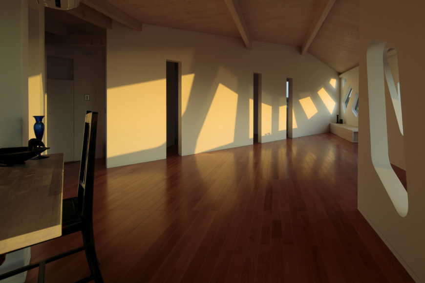 In the morning sunrise, light cascades throughout the interior, casting polygonal shapes across the slit-divided walls. Here we see the natural wood on floor and ceiling bookending the white wall spaces.