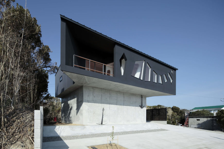 Facing toward the East, we see the elevated black body of the home standing over its concrete perch, with a pair of anchors below. The wave-shape windows stand next to sheltered balcony space.