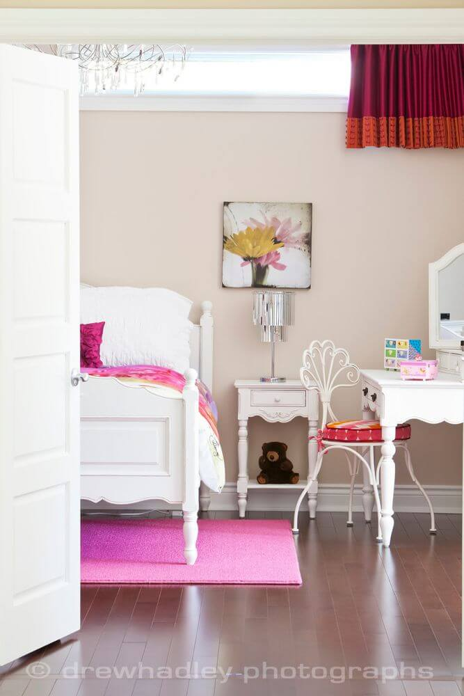 Children's bedroom pairs pink and white details over the hardwood flooring, with small arrow foot desk at right, next to wood frame bed.