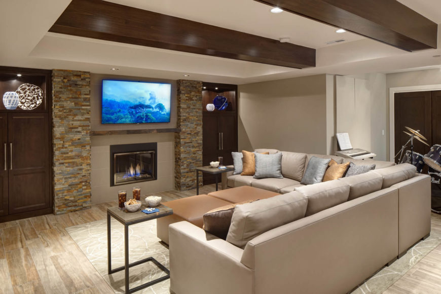 Massive L-shaped sectional defines this relaxing space, with a pair of light brown cubic ottomans at center. The porcelain plank floor tiling can be seen throughout, with its white-washed hardwood look. Exposed maple beams overhead aid in the rustic feel.