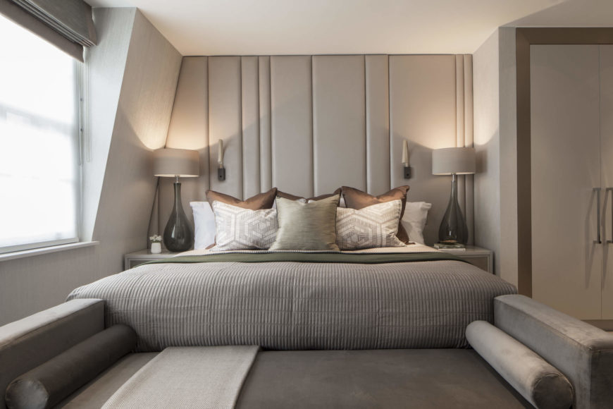 The primary bedroom continues the unifying neutral, grey toned theme. Backless sofa stands at the foot of the bed, making for a continuous relaxation piece.