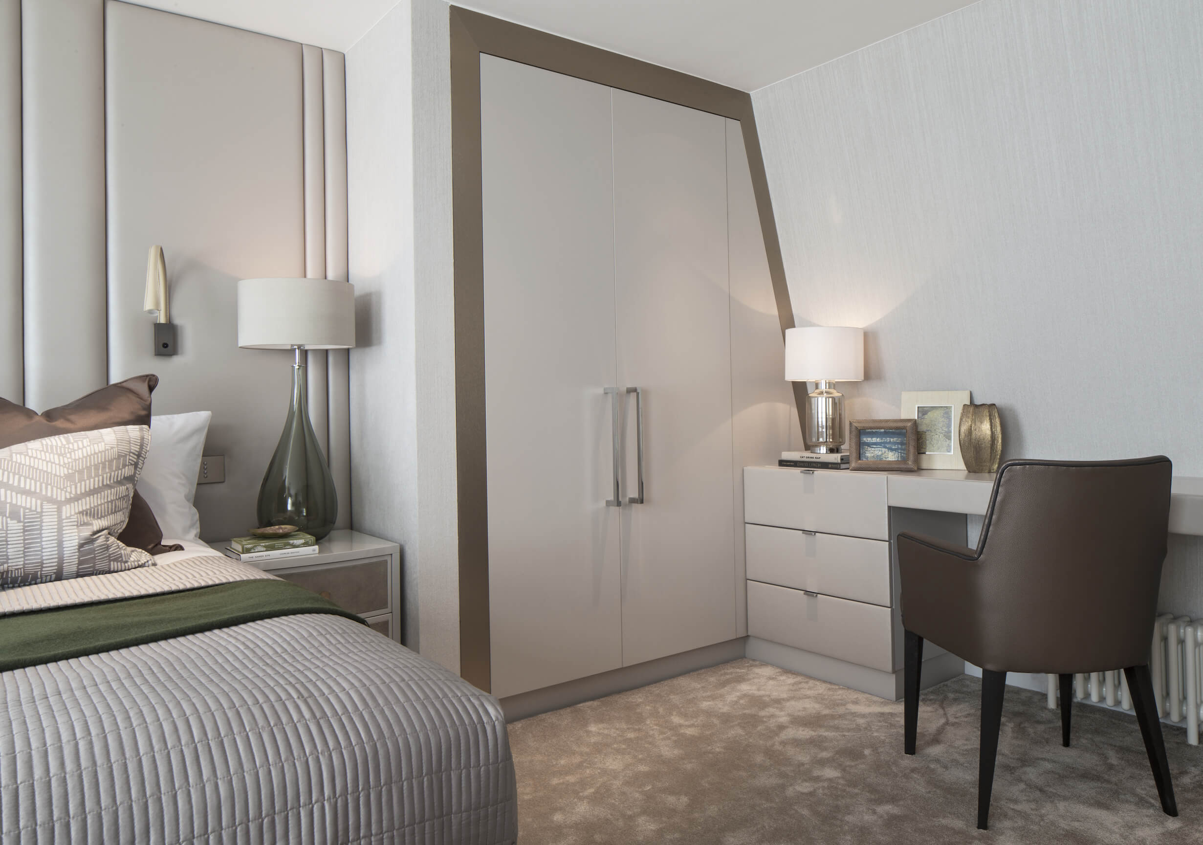 With angled walls leaning toward the ceiling, this space grants a cozy feel to the bedroom. Light toned, minimalist desk design at right contrasts with dark mocha leather chair.