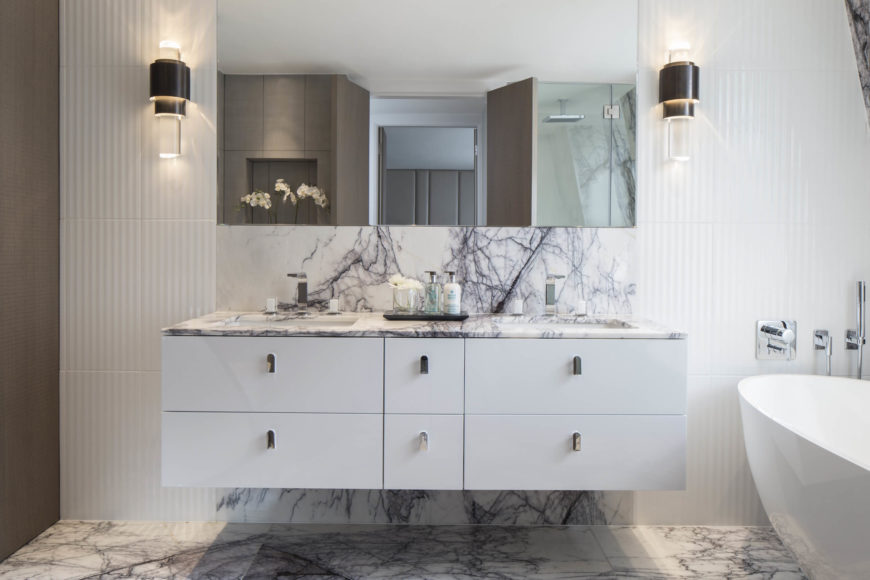 Primary bath holds a striking use of textural marble, with flooring reaching up through the floating white vanity to encompass a backsplash space. Modernist cylindrical sconces flank the frameless mirror on a rippled texture wall.