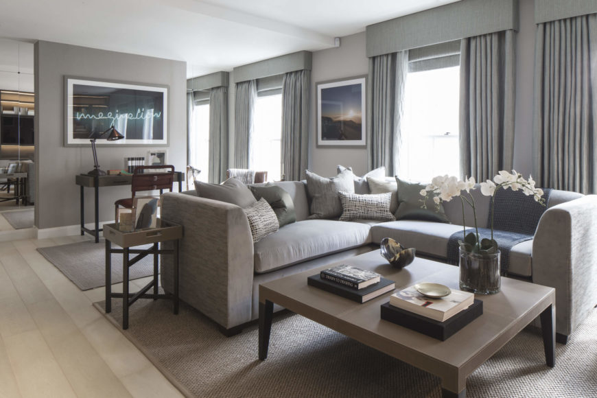The open design living room layers a series of neutral grey tones over the lightly bleached natural hardwood flooring. Dark and light toned wood tables and desk punctuate the grey space, along with a selection of art pieces.